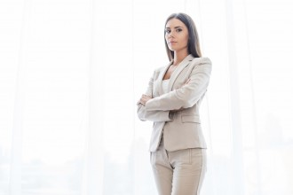 Confident young businesswoman in suit keeping arms crossed and looking at camera