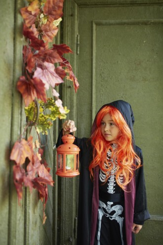 Portrait of Halloween girl with lantern standing by the door of dilapidated house