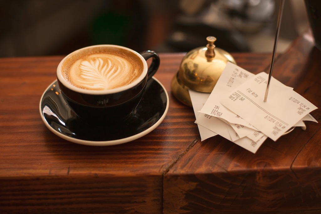 A latte and receipts at a European cafe.