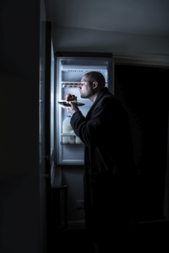 a bald man in his dressing gown sniffing and savouring a slab of cake left in the fridge.