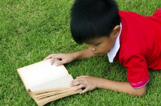 Children reading at a lawn as a backdrop.