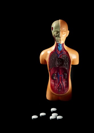 Medication, with plastic human body anatomy on black