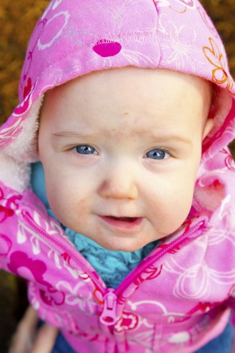 A young infant girl in pink is photographed outdoors for this child portrait.
