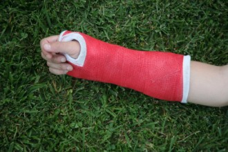 Red wrist arm and hand cast on green grass background