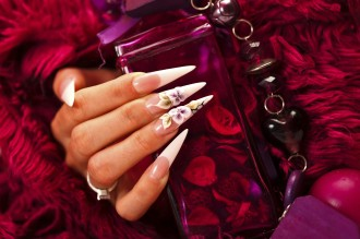 A woman's hand with long artificial nails holdig a beauty purple bottle. Closeup view.