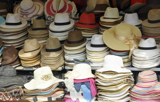 market stall with many hats in straw hats for sale in various sizes
