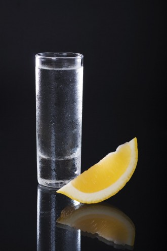 Shot glass filled with clear alcohol on a black background