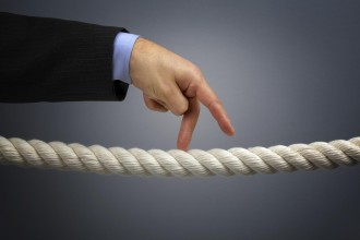 Businessmans fingers walking the tightrope concept for business risk or leadership