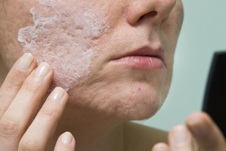 Cream applying to problematic female skin with acne scars