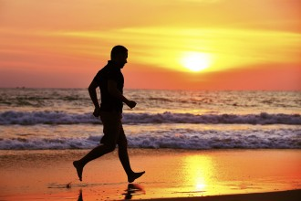Young man is running on the beach at sunset.