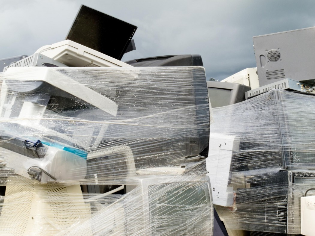 Stacked high pile of obselete electronic equipment and computer parts wrapped in plastic for recycling or proper disposal