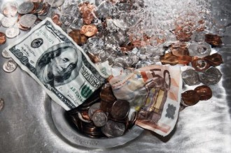 Money down the drain, dollar bill, Euro currency and  coins getting flushed down the drain. Wasting money, losing money, spending money