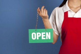 Female small business owner holding up OPEN sign