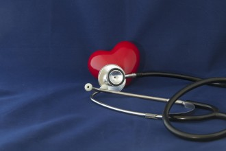 Red heart health checkup with stethoscope on blue background