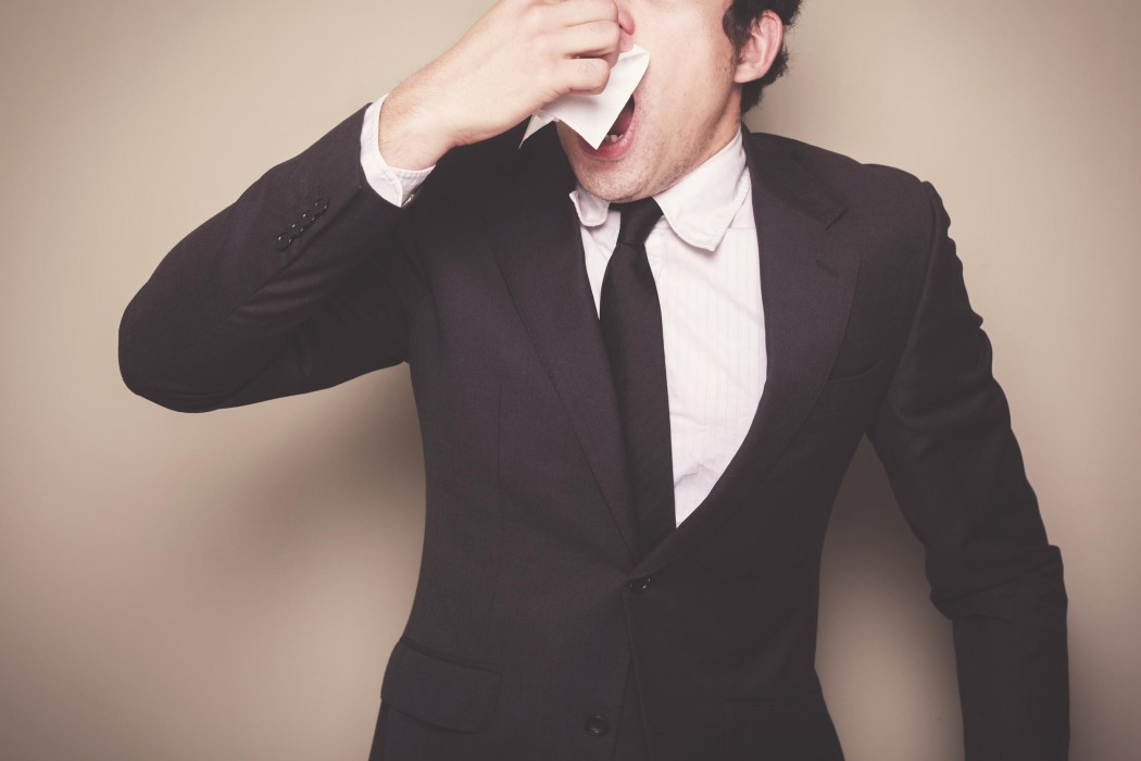 Businessman with a cold is sneezing
