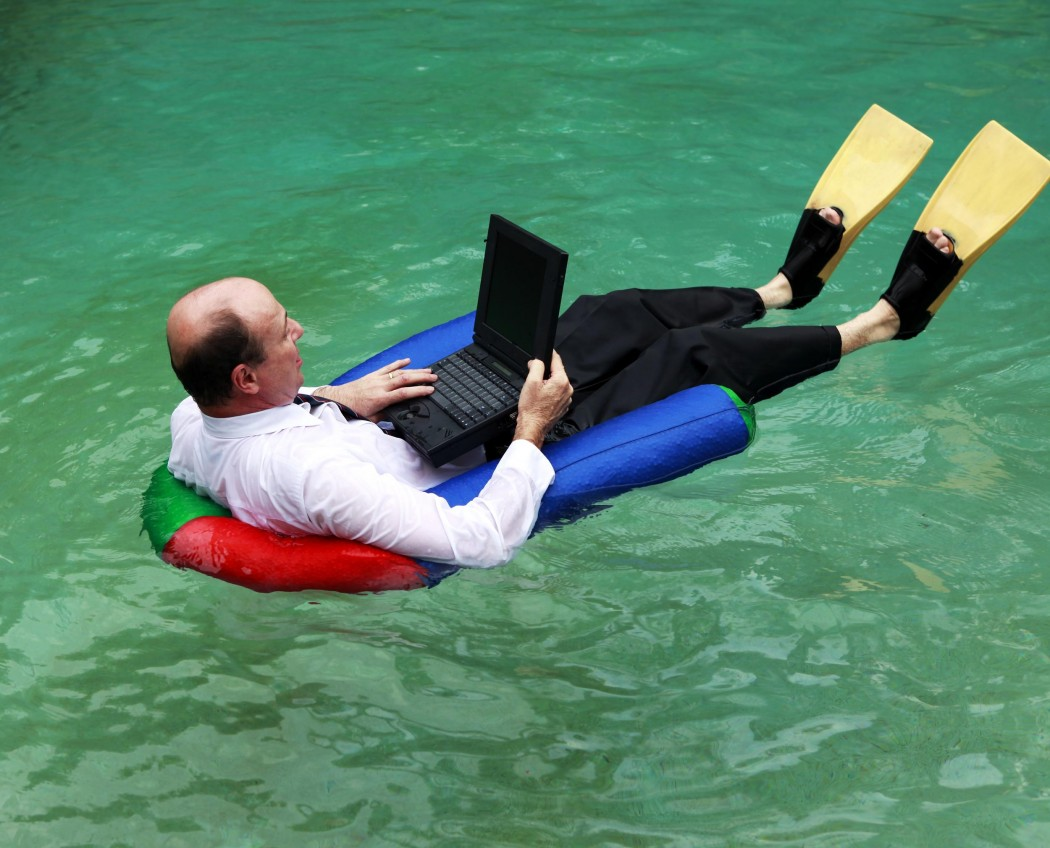 A businessman working from home dressed in business attire floating in a swimming pool on his laptop and wearing yellow flippers.