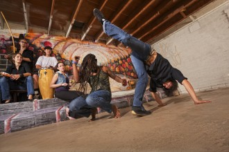 Group of six capoeira performers in urban building