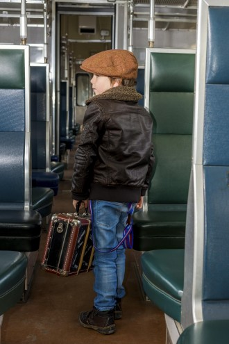 boy traveling in a train with his suitcase