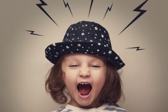 Angry shouting kid with lightnings above the head on grey background
