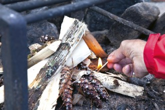 A camper holds a lit match under the kindling to start a camp fire.