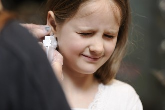 Young girl getting her ears pierced for the first time.