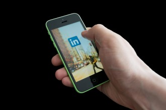 BUCHAREST, ROMANIA - MARCH 17, 2014: Photo of a hand using linkedIn app on iphone 5C. LinkedIn becomes more and more used by Romanian employers.