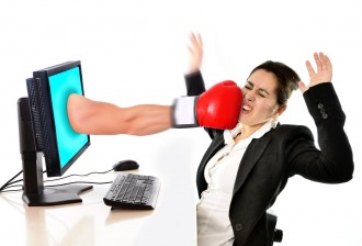 business woman sitting on desk with with computer hit by boxing glove coming out of monitor in social media network , mobbing, bullying, cybermobbing , cyberbullying  and stress at work concept