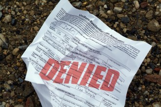 "A crumpled up home loan application (stamped with the word ""denied"") has been discarded on the ground in disappointment and frustration.  All information written is fictional."