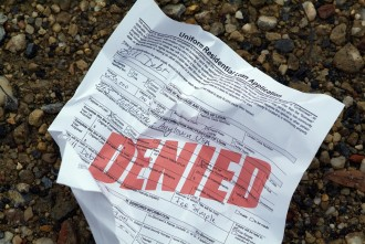 """A crumpled up home loan application (stamped with the word """"denied"""") has been discarded on the ground in disappointment and frustration.  All information written is fictional."""