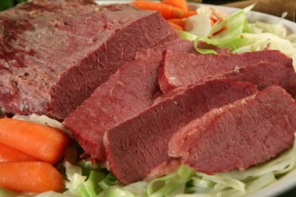 a flat cut corned beef brisket served with carrots and cabbage