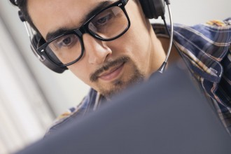 Young software engineer working in office with headphones on his head