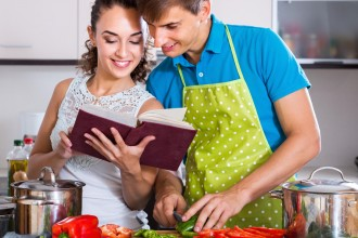 Smiling couple standing with cookbook in domestic kitchen
