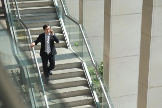 Entrepreneur going downstairs and talking on the phone
