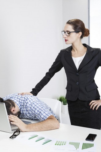 Angry female boss harassing her nerdy worker (mobbing concept)
