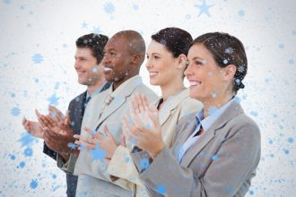 Side view of clapping sales team standing together against snow falling