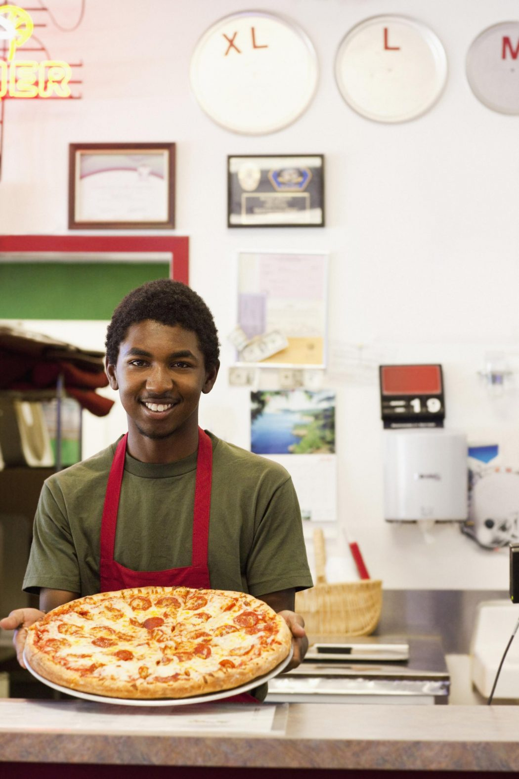 Black teenager working in pizza restaurant