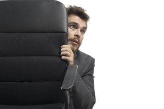 Concept of fear of a businessman behind a chair