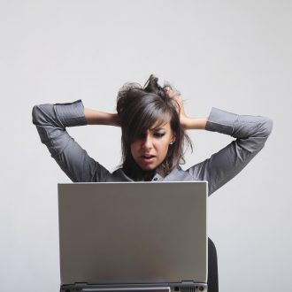 Frustrated young businesswoman looking at her computer