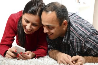 Cheerful couple playing game on mobile phone