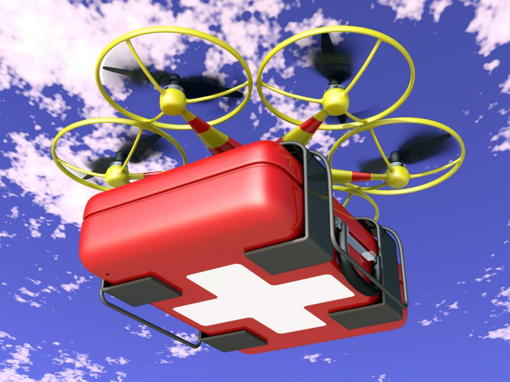 flying drone transports the a red suitcase with white cross