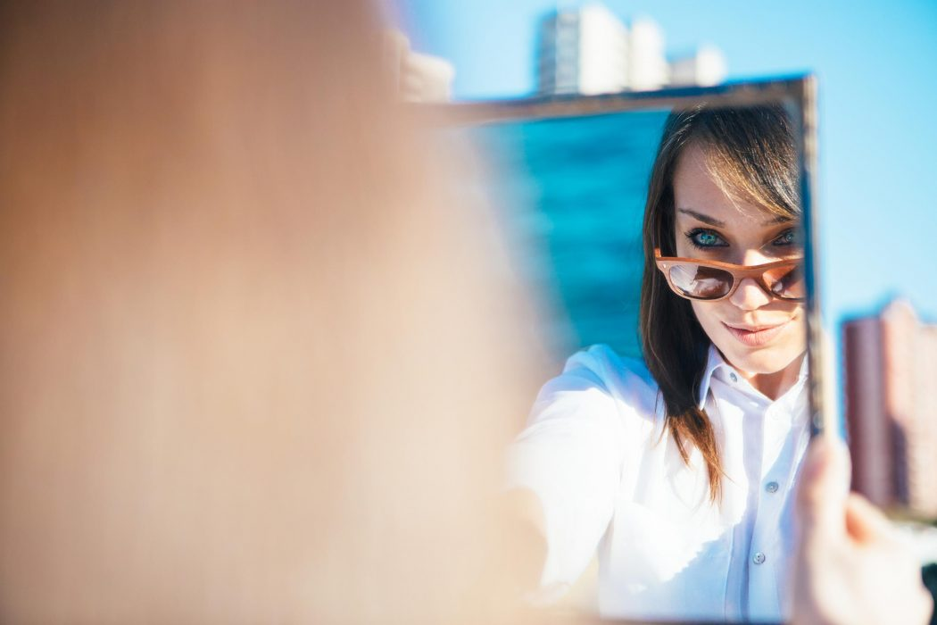 Over shoulder view of brunette beautiful woman with sunglasses in mirror reflection