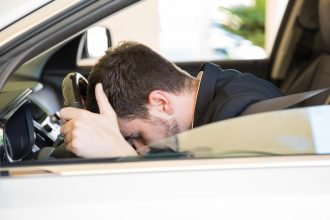 Profile view of a stressed and frustrated young businessman feeling down while driving a car