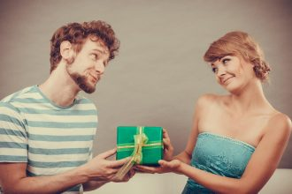Couple sitting on couch at home. Young man giving woman gift box filtered photo